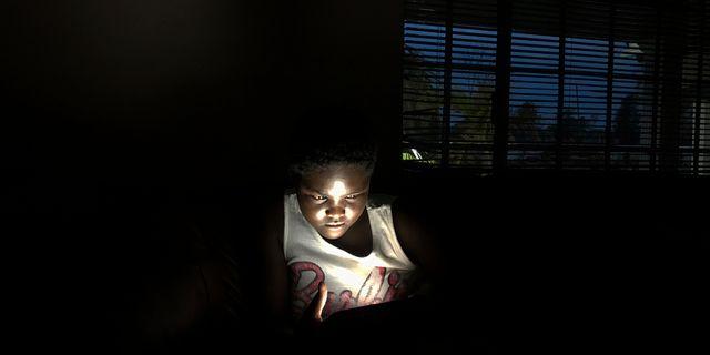 En ung flicka använder solenergi för att ladda sin telefon. Tsvangirayi Mukwazhi / TT NYHETSBYRÅN