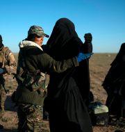 Mars 2019. USA-stödda Syriska demokratiska styrkorna undersöker en kvinna som lämnar det sista området i Syrien som hölls av IS. Felipe Dana / TT NYHETSBYRÅN