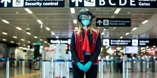 """En anställd bär en """"smart hjälm"""" som ska skanna av kroppstemperaturen hos resande på flygplatsen i Rom i början av maj. Roberto Monaldo / TT NYHETSBYRÅN"""