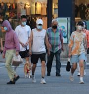 Personer i Taipei skyddar sig mot viruset genom att bära munskydd.  Chiang Ying-ying / TT NYHETSBYRÅN