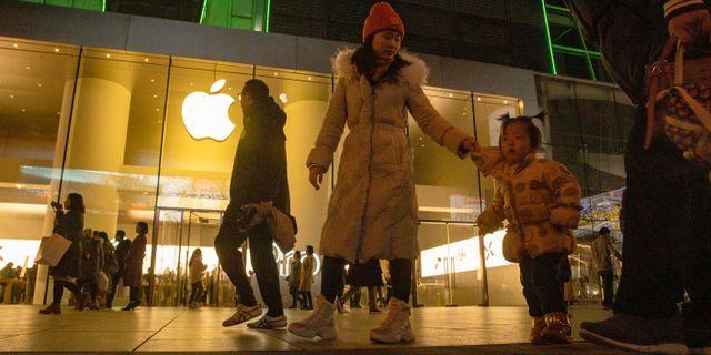 En kvinna och ett barn vandrar förbi Apples butik i Peking i december 2019. Ng Han Guan / TT NYHETSBYRÅN