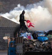 En man lastar tillhörigheter på en lastbil, efter att ha satt eld på sitt hus, i ett område som ska lämnas över till Azerbajdzjan. Dmitry Lovetsky / TT NYHETSBYRÅN