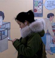 Illustrationsbild: Kvinna med Iphone i Pekings tunnelbana. Andy Wong / TT NYHETSBYRÅN