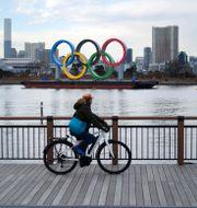 En man cykar förbi de olympiska ringarna i Odaiba i Tokyo, 8 januari, 2020. Eugene Hoshiko / TT NYHETSBYRÅN