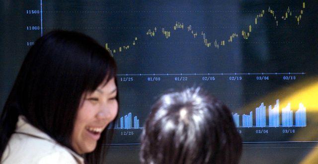 Kvinna går förbi skärm med börskurser i Tokyo. Arkivbild. CHIAKI TSUKUMO / TT NYHETSBYRÅN