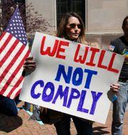 En kvinna demonstrerar mot coronarestriktionerna i Virginia. KEVIN LAMARQUE / TT NYHETSBYRÅN