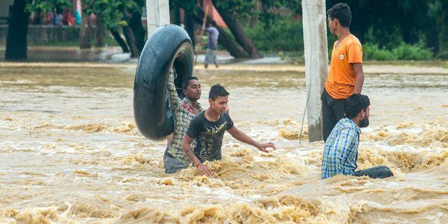 Nepaleser vadar genom vattenmassorna i distriktet Birgunj Parsa.   MANISH PAUDEL / AFP