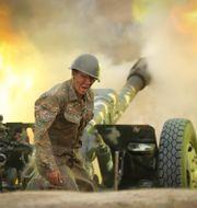 En armenisk soldat skjuter mot Azerbajdzjan. Sipan Gyulumyan / TT NYHETSBYRÅN