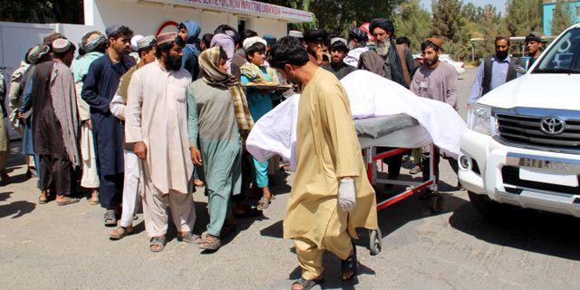 En död kropp fraktas iväg efter attacken. NOOR MOHAMMAD / AFP