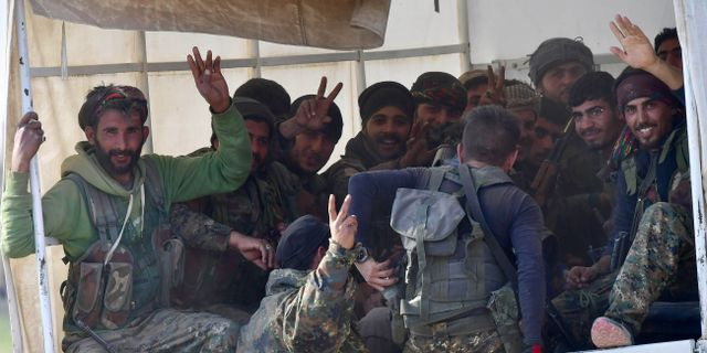 SDF-soldater gör segertecknet på väg tillbaka från strider mot IS i Baghouz. Arkivbild från den 19 mars.  GIUSEPPE CACACE / AFP