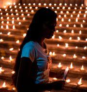 Sörjande tänder ljus en vecka efter attackerna.  JEWEL SAMAD / AFP