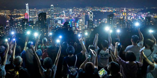 """Demonstranter bildar en mänsklig kedja och håller upp sina mobiltelefoner på """"the Peak"""", en populär plats för turister att besöka i Hongkong. Kin Cheung / TT NYHETSBYRÅN"""