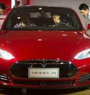 Besökare testar en Tesla Model S vid bilmässa i Peking. Arkivbild. Mark Schiefelbein / TT NYHETSBYRÅN