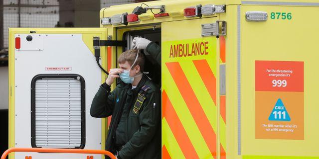 En ambulanssjukvårdare får hjälp att ta på sig munskydd av en kollega. Kirsty Wigglesworth / TT NYHETSBYRÅN