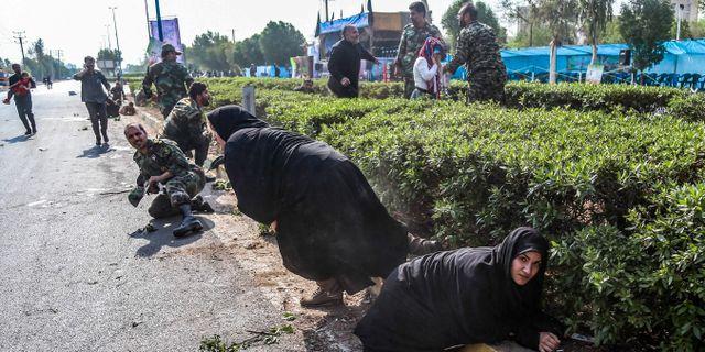 Människor görmmer sig under attacken.  MORTEZA JABERIAN / ISNA