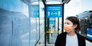 Kvinna med munskydd vid en busshållsplats.  Erik Simander/TT / TT NYHETSBYRÅN
