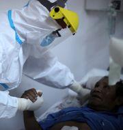 Läkaren Matias Norte tröstar en patient med covid-19 på ett sjukhus i Buenos Aires. Natacha Pisarenko / TT NYHETSBYRÅN