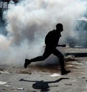 Person springer genom tårgas. Arkivbild.  Themba Hadebe / TT NYHETSBYRÅN