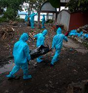 Personer med skyddskläder i Indien som bär på en kropp.  Anupam Nath / TT NYHETSBYRÅN