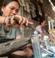 Indonesiska kvinnor som tillverkar hantverksprodukter att sälja på en turist-marknad på Bali.  Shutterstock
