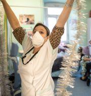 En sjuksköterska sätter upp glitter på ett äldreboende i Frankrike. Jean-Francois Badias / TT NYHETSBYRÅN