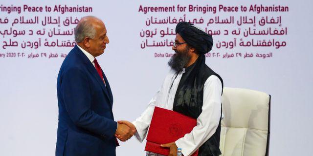 Mulla Abdul Ghani Baradar och USA:s sändebud Zalmay Khalilzad skakar hand efter avtalet i helgen. IBRAHEEM AL OMARI / TT NYHETSBYRÅN