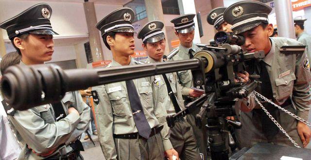 Arkivbild på när kinesiska säkerhetsvakter kollar på ett vapen under ett polisseminarium i Peking. Anonymous / TT NYHETSBYRÅN