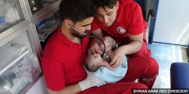 Sjukvårdspersonal håller Nawras och Moaz. Syriska röda halvmånen.
