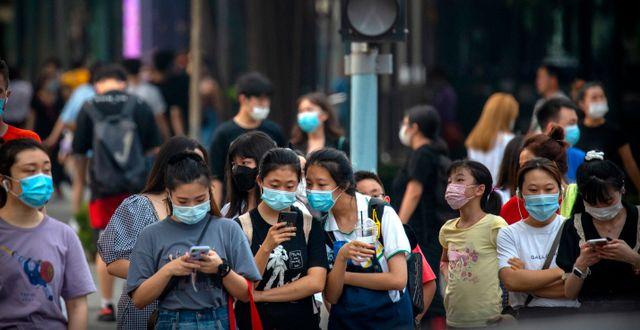 Människor med munskydd i Kina. Mark Schiefelbein / TT NYHETSBYRÅN