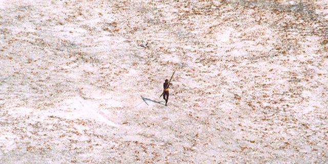 En man från stammen riktar sin pilbåge mot en helikopter från indiska sjöräddningen som flyger över ön i samband med tsunamikatastrofen 2004.  Handout / TT NYHETSBYRÅN