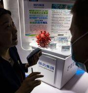 En kvinna som jobbar på Sinopharm berättar om företagets arbete med ett coronavaccin. Ng Han Guan / TT NYHETSBYRÅN