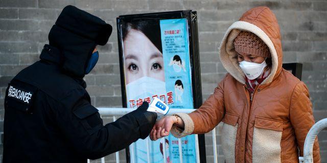 Människor med munskydd i Peking. Andy Wong / TT NYHETSBYRÅN