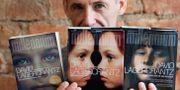 Författaren David Lagercrantz med böcker från Millenium-serien.  Henrik Montgomery/TT / TT NYHETSBYRÅN