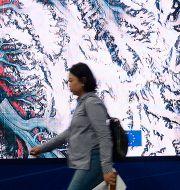 Arkivbild. Mötesdeltagare passerar framför en satellitbild som visar utsläpp av växthusgaser. Czarek Sokolowski / TT NYHETSBYRÅN
