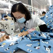An employee wearing a face mask to protect herself against the coronavirus stitches clothing for export at a factory in Donghai county in eastern China's Jiangsu Province, Tuesday, Oct. 27, 2020. China's export growth accelerated in October, boosting the total so far this year back above pre-coronavirus levels for the first time. TT NYHETSBYRÅN