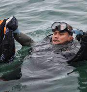Dykare samlar in sådant som kommer från det kraschade planet. TT NYHETSBYRÅN