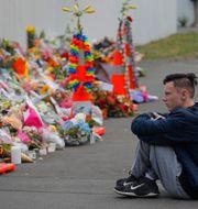 En student sitter vid havet av blommor vid attentatsplatsen i Christchurch.  Vincent Yu / TT NYHETSBYRÅN
