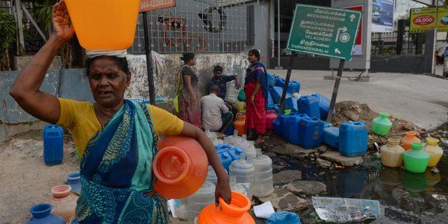 Indier hämtar vatten från en kommunal brunn i Chennai när vattenreservoarerna i staden tömts.  ARUN SANKAR / AFP