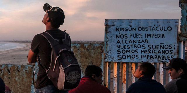 Migranter vid gränsstaketet i Playas de Tijuana. GUILLERMO ARIAS / AFP