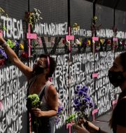 Kvinnor sätter fast blommor på ett staket i Mexico City, där namnen på mördade kvinnor skrivits. Eduardo Verdugo / TT NYHETSBYRÅN