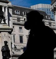 Illustrationsbild. Person med ansiktsmask går förbi Bank of Englands byggnad i London.  Toby Melville / TT NYHETSBYRÅN