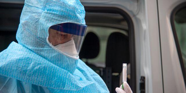En ambulanssjukvårdare visar upp ett provtagningskit. Ambulansen gör hembesök hos personer som misstänks vara smittade av Corona. Anders Wiklund/TT / TT NYHETSBYRÅN