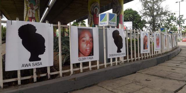 Porträtt i en rondell i Lagos som föreställer några av flickorna som fördes bort. PIUS UTOMI EKPEI / AFP