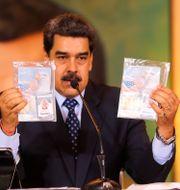 Nicolás Maduro visar upp tillfångatagna Luke Denmans och Airan Berrys id-handlingar. TT NYHETSBYRÅN