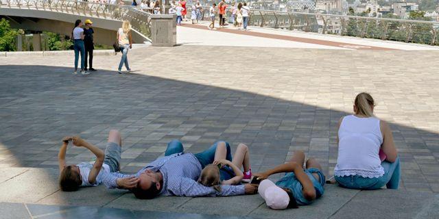 En familj svalkar sig under värmebörjan.  SERGEI SUPINSKY / AFP