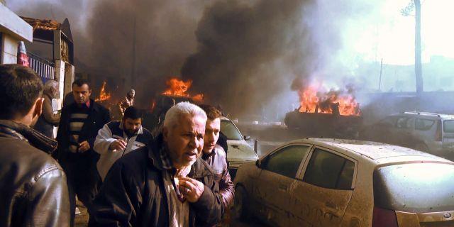 Människor i närheten av platsen för bombdådet i staden Azaz i Syrien. STRINGER / AFPTV