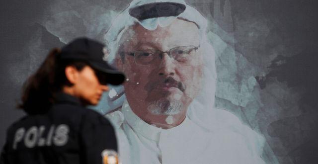 Jamal Khashoggis bild på en vägg samt en polis.  Lefteris Pitarakis / TT NYHETSBYRÅN