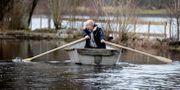 Mikael Jönsson i Åled tar båten mellan hemmet och bilen, vägen är översvämmad. ADAM IHSE / TT / TT NYHETSBYRÅN