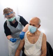 En man får vaccin i en gymnastiksal i Rinkeby som förvandlats till vaccinationscentral.  Fredrik Sandberg/TT / TT NYHETSBYRÅN