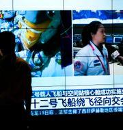 Kinesisk tv visar bilder på taikonauterna inuti rymdfarkosten på väg tillbaka till jorden.  Andy Wong / TT NYHETSBYRÅN